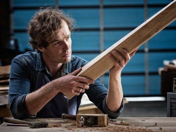 Lars Wilmer begutachtet ein Stück Holz